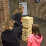 A student and two young girls play Jenga.