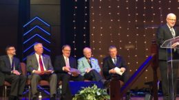 John Bray speaks about the service while (from right to left) Dr. Wright, Wilbur Willims, Dr. Newman, Mayor Alambaugh and Superintendent Wayne Smith sit behind him.